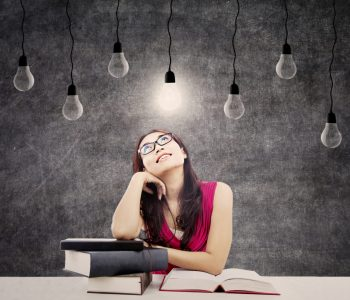 Portrait of smart female college student with books and bright light bulb above her head as a symbol of bright ideas