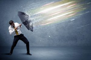 49546317 - business man defending light beams with umbrella concept on background