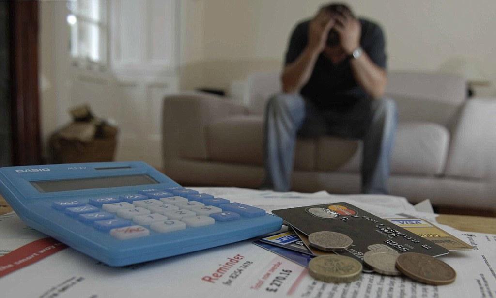AY7AXR man holds head in hands, credit cards bills money for debt