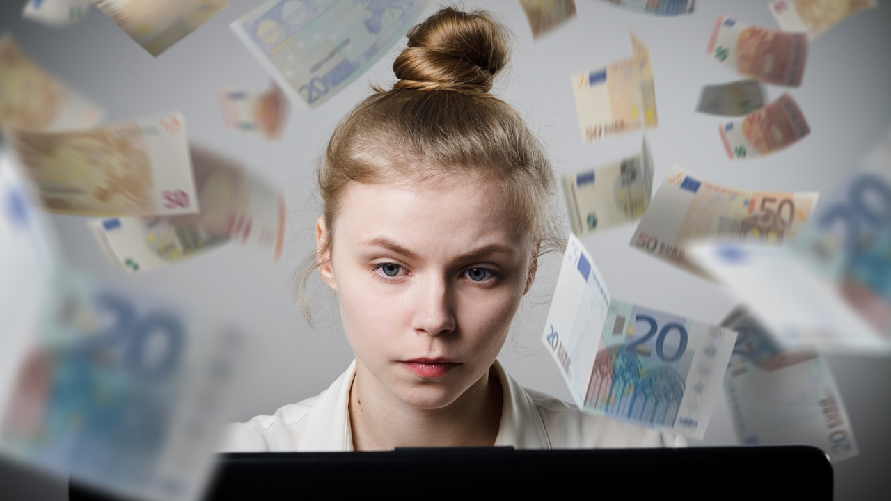 Young slim woman using a laptop to browse the net. Woman earns money on the internet.